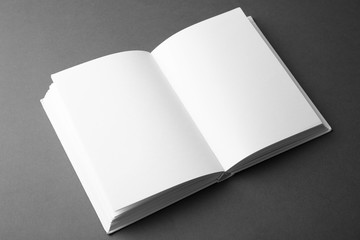 Open book with blank pages on dark grey background. Mock up for design
