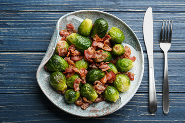 Printed kitchen splashbacks Brussels Tasty roasted Brussels sprouts with bacon on blue wooden table, flat lay