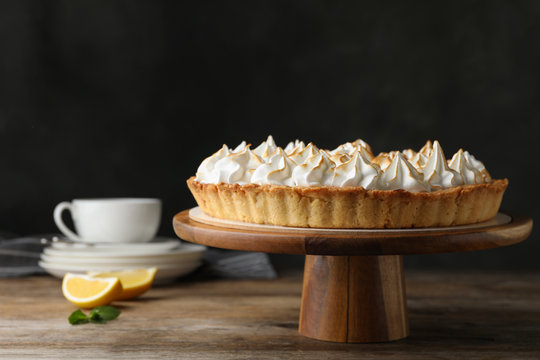 Stand with delicious lemon meringue pie on wooden table against black background