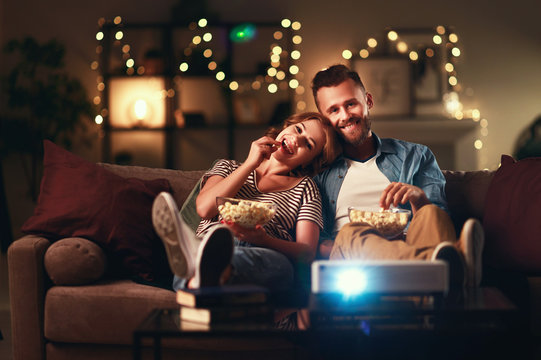 Family couple watching television projector at home on sofa.