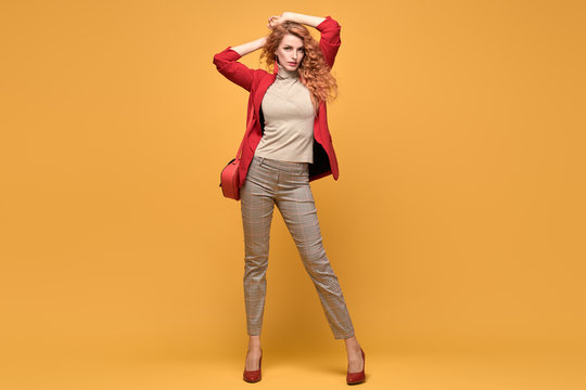 Fashionable woman in Trendy autumn spring outfit, stylish wavy hair, makeup. Joyful lady in red jacket smiling dance on orange. Cheerful girl, stylish fashion accessories, beauty style