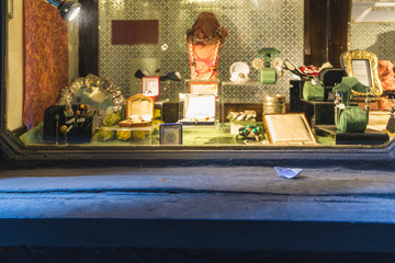 Small paper boat in front of a shop window with jewelry