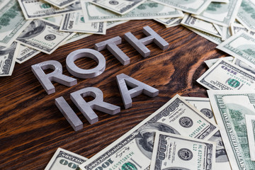 words ROTH IRA laid on wooden surface by metal letters with us dollar banknotes
