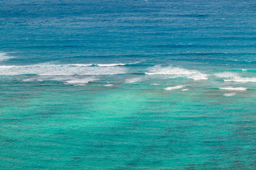 Beautiful blue green turquoise teal shallow tropical water with waves breaking on a coral reef on Oahu, Hawaii, USA