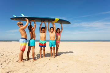 Many kids carry surfboard on the beach to sea