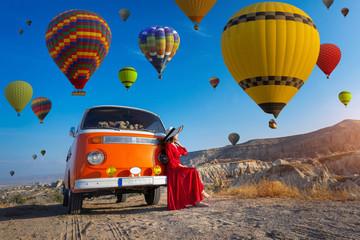 Wall Mural - Beautiful girl looking at hot air balloons in Cappadocia, Turkey.