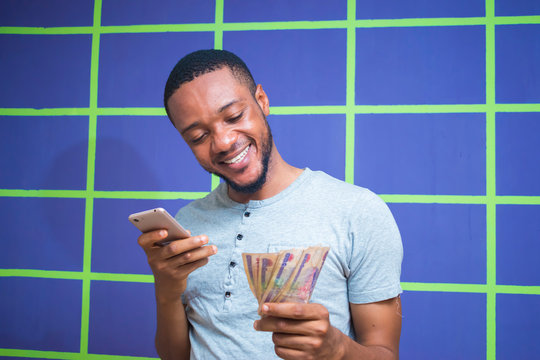 a young Nigerian man got surprised by what he saw on his smartphone and holding his money