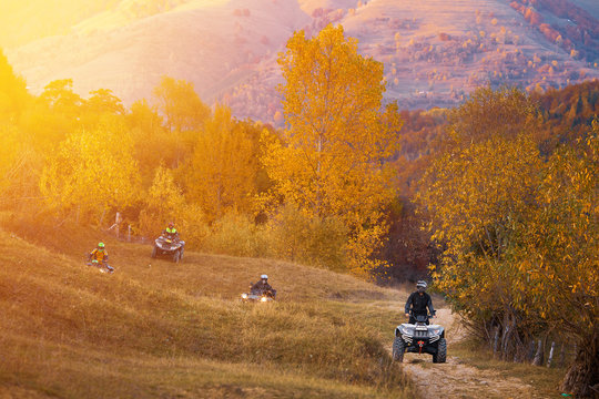 All terrain vehicles, quad bikes, atv, riding through beautiful rural scenery in autumn