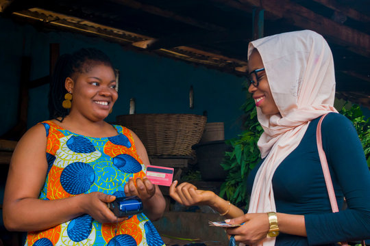market woman receiving credit card from her customer  to pay her bills