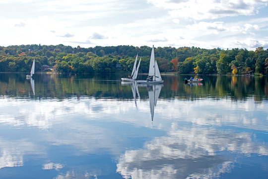 A light breeze sends ripples to the calm waters of Mystic Lake in Arlington, Massachusetts with reflecting white cumulus clouds on the lake's waters. -11