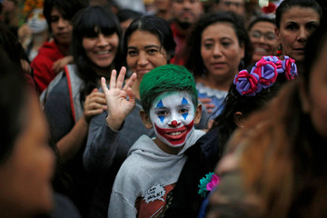 A child with his face painted as movie character Joker participates the annual Catrina parade ahead of the Day of the Dead in Mexico City