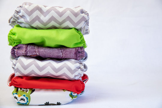 pile of eco friendly cloth nappies / diapers on a white background