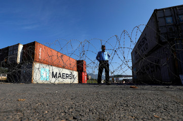 A police officer stands behind barbed wires near the shipping containers used to block the road ahead of Azadi March in Islamabad,