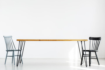 White room with two chairs at a long wooden table, real photo with copy space on empty wall
