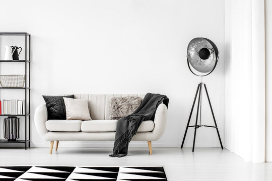 Industrial black lamp next to beige couch with blanket and pillows, copy space on empty white wall