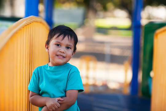 A cute little boy holding on to his arm after an injury at a kids playground.