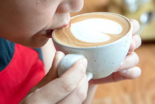 woman is drinking art latte coffee