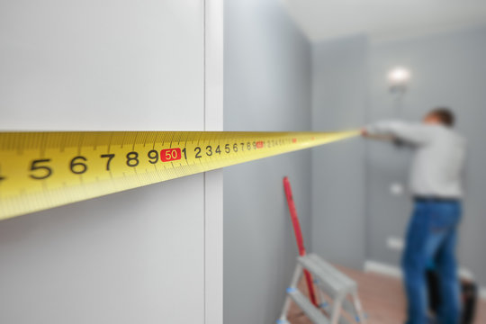 Man with tape-line measuring distance