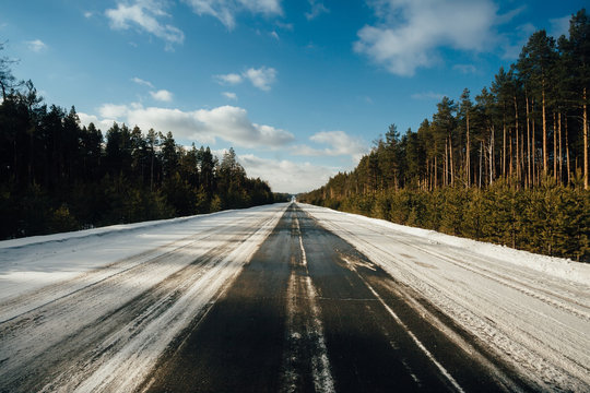 Ice on the road between the forests. Very slippery road