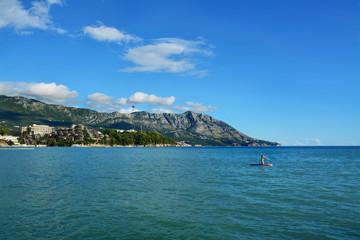 Obraz morze Adriatyckie, plaża i góry, Czarnogóra, surfer - fototapety do salonu