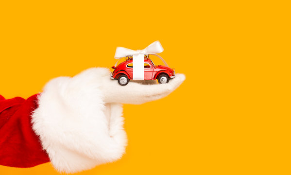 Santa Claus holding modern car with bow in hand over orange