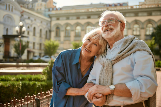 We love to travel together. Happy senior couple bonding to each other and smiling while standing outdoors