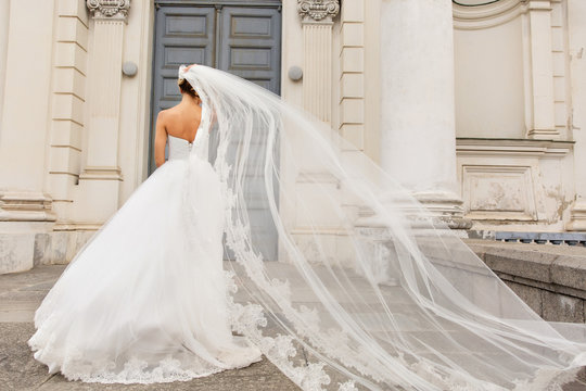 Wedding day. Bride in white wedding dress holding long veil with embroidery