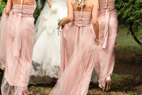 Bride and bridesmaids in pink dresses walking at wedding day. Happy marriage and wedding party concept