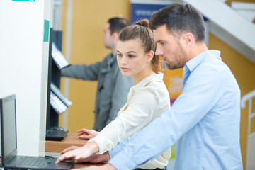 portrait of young woman and man looking at laptop