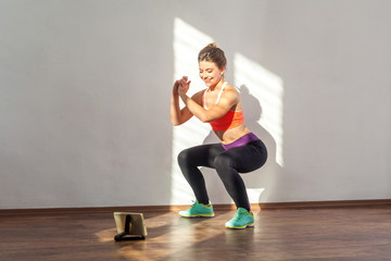 Positive sportive woman with bun hairstyle and in tight sportswear doing squatting sit-up exercise while watching training video on tablet. indoor studio shot illuminated by sunlight from window Fototapete
