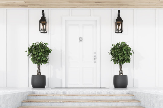 White front door of white house with trees, stairs