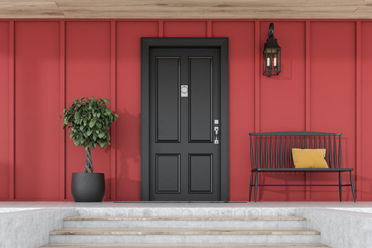 Black front door of red house with tree and bench