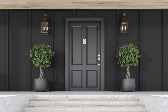 Black front door of black house with trees