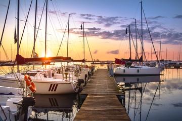 Boats docking in the marina at the Niegocin Lake during sunrise. Wilkasy, Masuria , Poland.