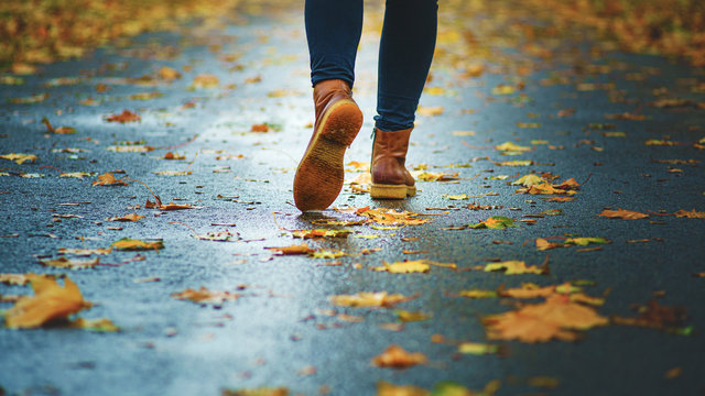Walk on wet sidewalk. Back view on the feet of a woman walking along the asphalt pavement with puddles in the rain. Pair of shoe on slippery road in the fall. Abstract empty blank of the autumn weathe