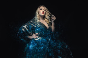 Half length plus size model shot with mixed lights effect. Black background. Young blonde woman in shiny evening dress posing towards the camera. Fashion glamour shooting.
