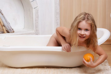 4 years old girl stretches out of a milk bath for an orange