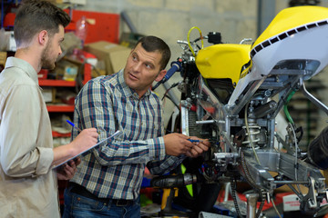 repairing a motorcycle in a workshop with coleague