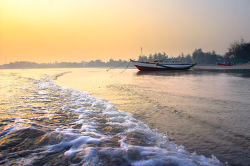 motion waterscapes of sea with beauty morning sunrise, boat in parking on sand in bengkulu