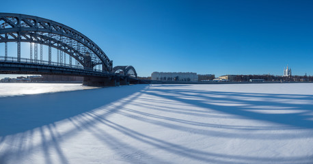 Saint Petersburg. Russia. Peter the Great Bridge. Bolsheokhtinsky bridge. Snow in St. Petersburg. Bridge casts a shadow. Bolsheokhtinsky Bridgework on the background of blue sky. Neva. Cities Russia