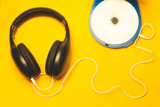 Headphones with a white cable on a yellow background. compact disc player with white cd and earphones