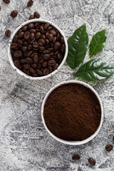 coffee beans and ground coffee in bowls with coffee tree leaf on a light background.