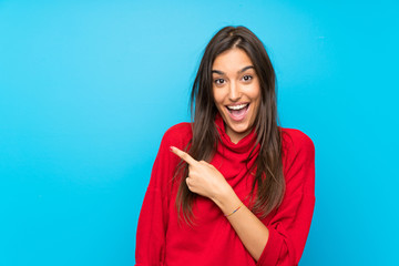 Young woman with red sweater over isolated blue background pointing finger to the side