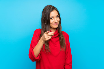 Young woman with red sweater over isolated blue background points finger at you