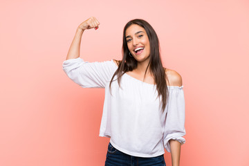 Young woman over isolated pink background doing strong gesture