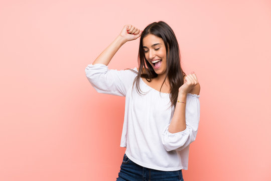 Young woman over isolated pink background celebrating a victory