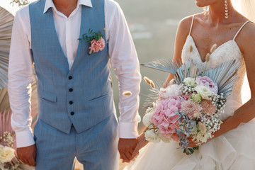 Happy bride and groom holding hands on wedding ceremony, copy space. Wedding couple in love, newlyweds. Bridal bouquet