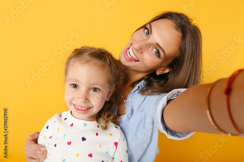 Woman in light clothes have fun, cute child baby girl 4-5 years old. Mommy little kid daughter doing selfie shot isolated on yellow background. Mother's Day love family parenthood childhood concept.