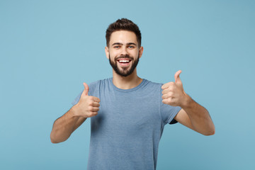 Young joyful funny smiling handsome man in casual clothes posing isolated on blue wall background, studio portrait. People sincere emotions lifestyle concept. Mock up copy space. Showing thumbs up. Papier Peint