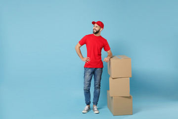 Delivery man in red uniform isolated on blue background, studio portrait. Male employee in cap t-shirt print working as courier dealer hold empty cardboard box. Service concept. Mock up copy space. Wall mural
